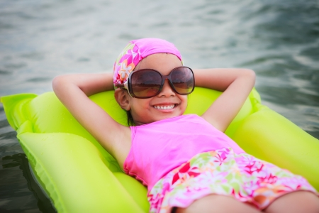 Little girl laying on tube swimming in the sea photo