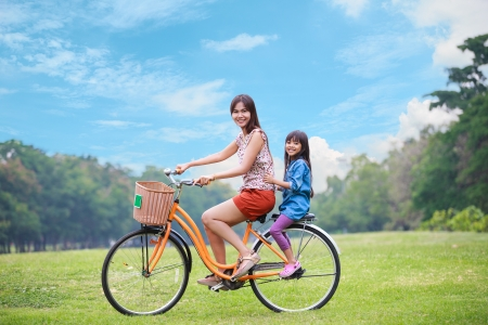asian family outdoor: Mother and a daughter cycling bicycle at the park