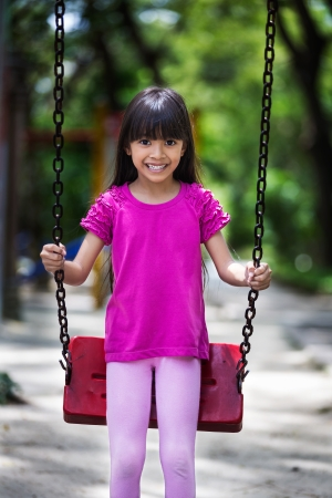 Happy asian little girl smiling on swing at park photo