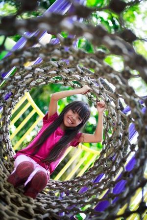 ni�os en recreo: Ni�a asi�tica disfruta jugando en un parque infantil, retrato al aire libre