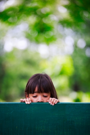 Sad little girl sits on bench at park photo