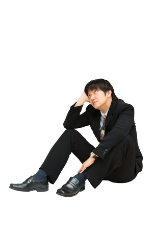 Young asian businessman sitting and looking up above his head, Isolated over white with clipping path photo