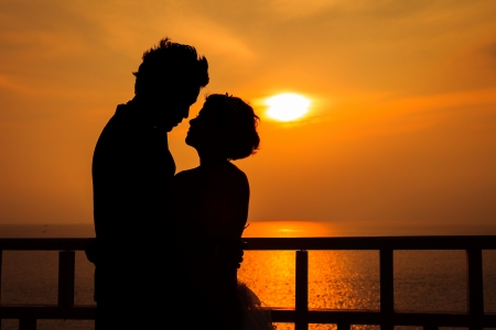 Couple silhouette on the beach at sunset photo