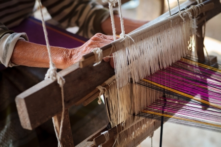 rug weaving: Close up of old woman weaving blue and white pattern on loom