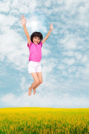 Little girl jumping against beautiful sky photo