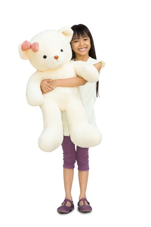 stuffed toy: Pretty little girl hugging big bear, isolated on white with clipping path Stock Photo