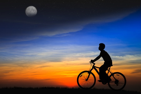 zon maan: Silhouet jongen rijden op een fiets op de zonsondergang Stockfoto