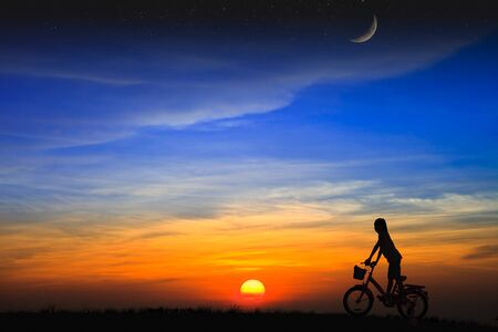 Silhouette daughter riding a bicycle on the sunset photo
