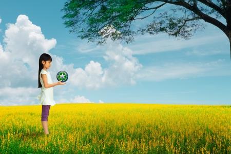 happy planet earth: Ni�a que sostiene la tierra con el s�mbolo de reciclaje en el campo de flores, los elementos de esta imagen proporcionada por la NASA