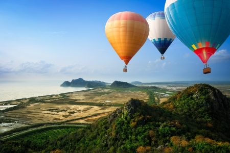 hot air: Hot air balloons floating up to the sky over mountain at the sea Stock Photo
