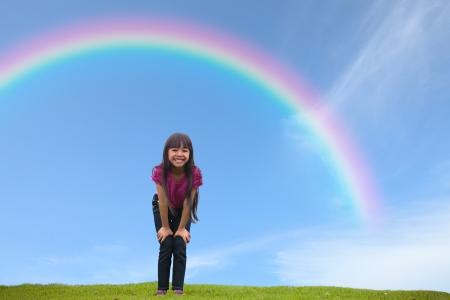 무지개 아래 녹색 잔디에 서 서 웃 고 아시아 소녀, 야외 초상화
