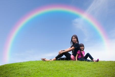 母と娘の空に虹を草の上に一緒に座っています。