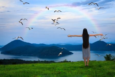 Meisje dat zich met open armen tegen de blauwe hemel met de regenboog Stockfoto