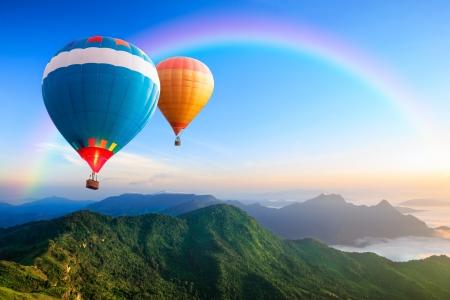 다채로운 뜨거운 공기 풍선은 산에 비행 스톡 콘텐츠