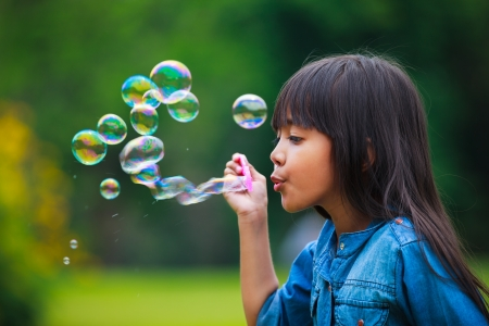 blowing bubbles: Asian little girl is blowing a soap bubbles, Outdoor Portrait