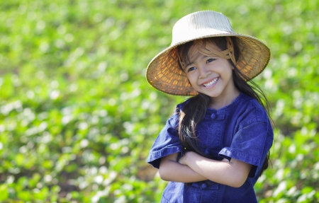Little smiling girl farmer on green fields, Outdoor portrait photo