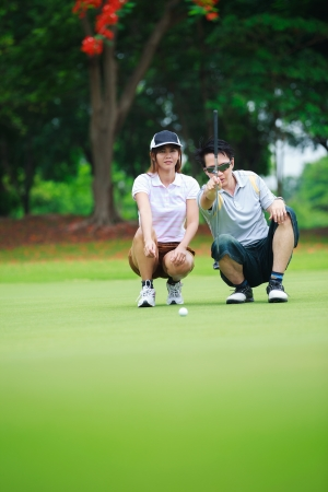 Professional teaching young woman golfer to play golf photo