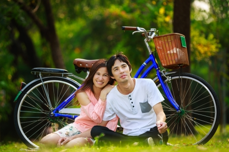 Young asian couple sitting on ground in park relaxing, Outdoor portrait photo