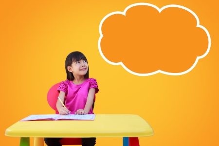 Portrait of a young girl in school at the desk  Vertical Shot  Daydreaming  Blank cloud with copyspace for your text and logo Stock Photo - 18058160