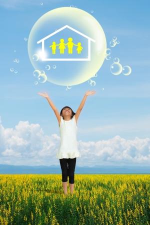 Sonrisa de la niña que muestra en símbolo de la familia en la burbuja de jabón grande en el campo de flor amarilla