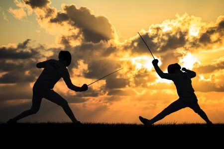 Silhouette fencers with sunset photo