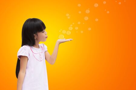 8 10 years: Asian little girl blowing soap bubbles Stock Photo