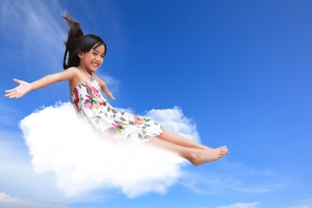 happily: Smiling little girl sitting on the cloud over sky