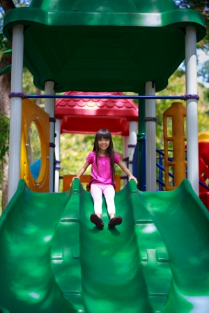 school playground: Smiling asian little girl sitting slide, Outdoor portrait