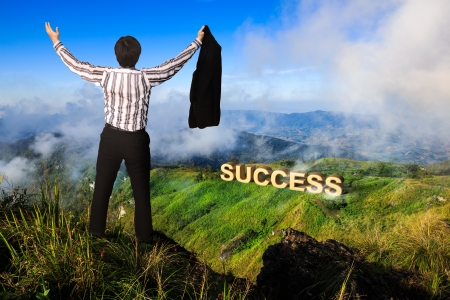 Businessman standing on a peak at mountain, Success in business concept photo
