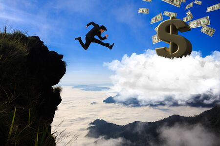 Businessman jumping from mountain to cloud, Business concept photo