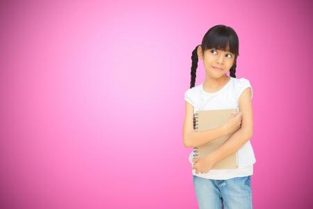 preteen girl: Asian little girl huging notebook looking empty space