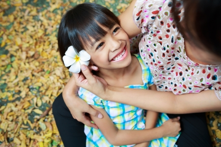 kids hugging: Mother and daughter sitting together in the park Stock Photo
