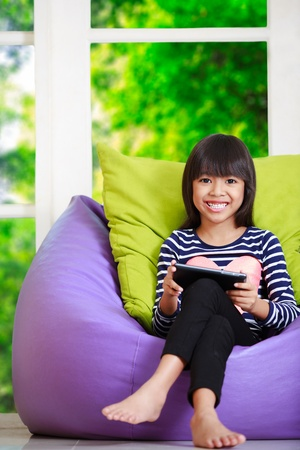 Little asian girl playing with tablet computer at home lying on sofa photo