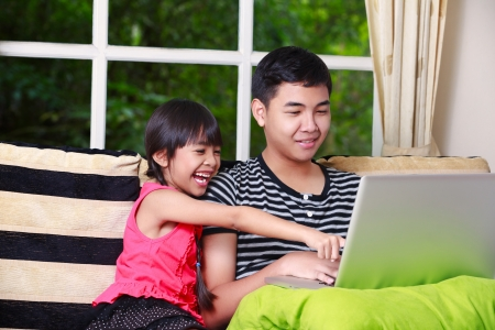 Little asian girl pointing on laptop with big brother at home photo
