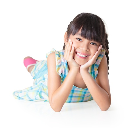 cute little girl smiling: Portrait of a cute happy little asian girl laying on floor, Isolated over white with clipping path