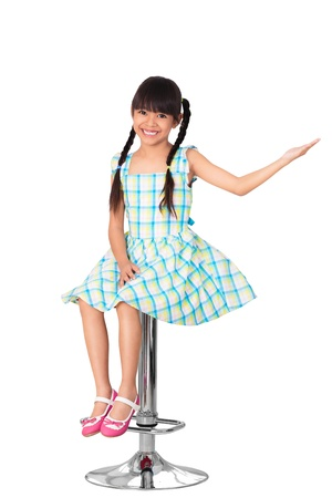 Happy little asian girl sitting on high chair, Isolated over white with clipping path Stock Photo