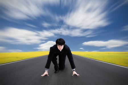 Young asian businessman kneeling as if about to start a race photo