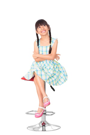 Portrait of happy little asian girl sitting on high chair, Isolated over white with clipping path photo