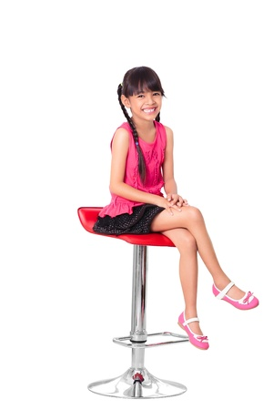 isolated chair: Portrait of happy little asian girl sitting on high chair, Isolated over white with clipping path