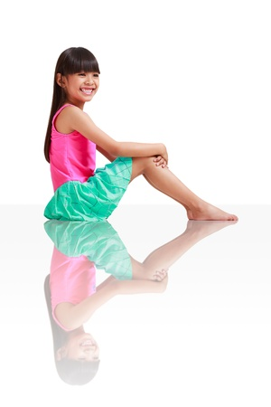Little asian girl wearing swimsuit sitting on the floor, Isolated over white photo