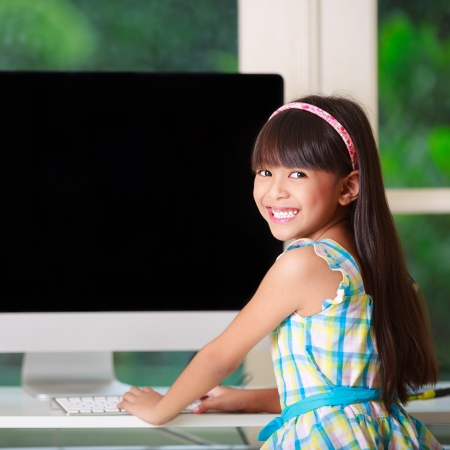 Little asian girl with computer at home Stock Photo - 19730663