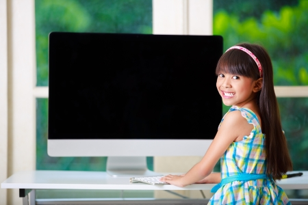 Little asian girl  with computer at home photo