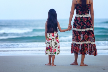 Rear view of a mother and daughter standing on the beach photo