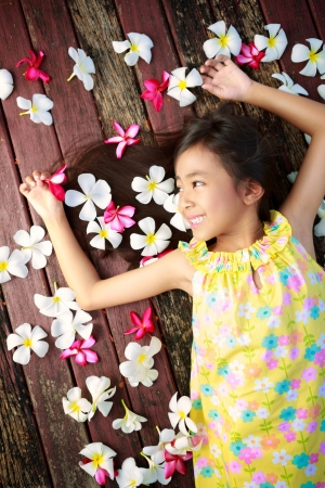 Little asian girl laying on the floor with petals on hair photo