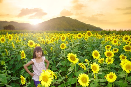 Closeup smiling girl in the sunflowers field with sunflowers photo