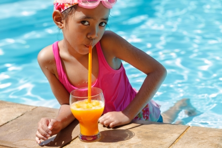 Little asian girl in the swimming pool, Drinking orange juice photo