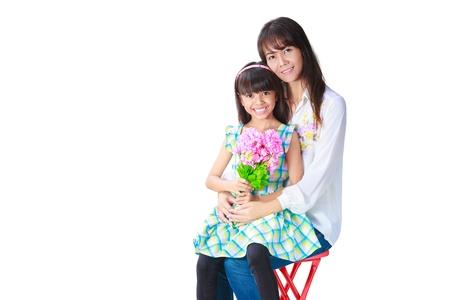 mother and daughter: Madre abrazando a su hija que han presentado su el ramo de flores, aislado en blanco