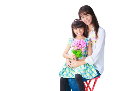 blonde mom: Mother hugging her daughter that have presented her the bunch of flowers, Isolated on white Stock Photo