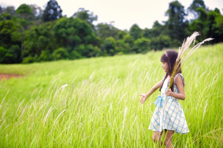 Little asian girl walking outdoors in a meadow photo