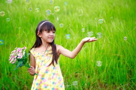 pequeño: Retrato de la niña disfrutar con pompas de jabón en la pradera verde, retrato al aire libre